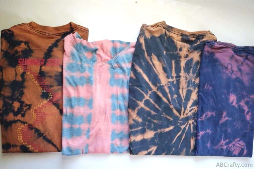 4 folded up reverse tie dye t shirts with different tie dye patterns