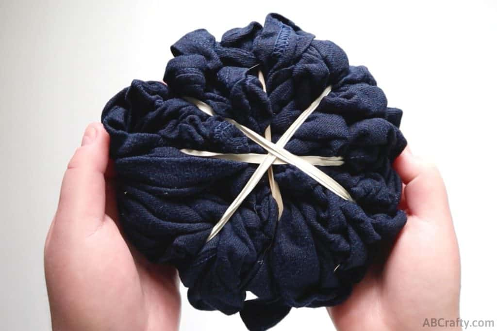 holding a navy shirt bundled up and wrapped diagonally in rubber bands