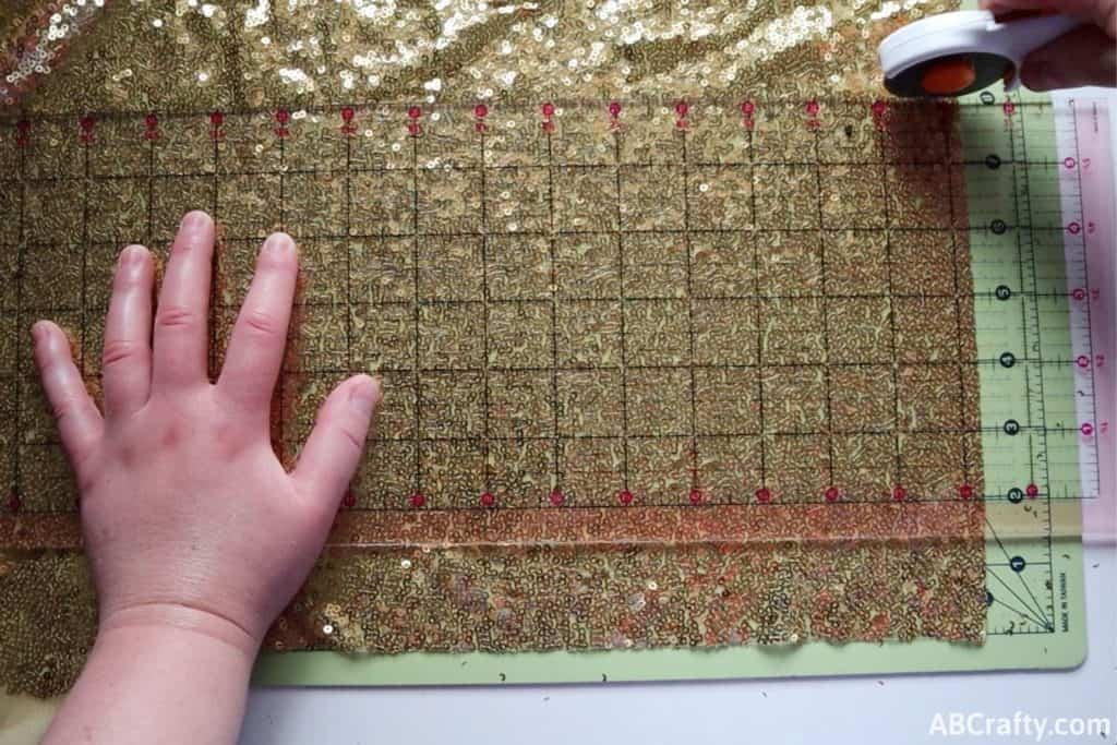 using a rotary cutter to cut a rectangle of gold sequin fabric