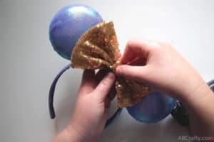 glueing a gold bow onto a blue and purple iridescent mickey ears to finish the disney world 50th anniversary ears