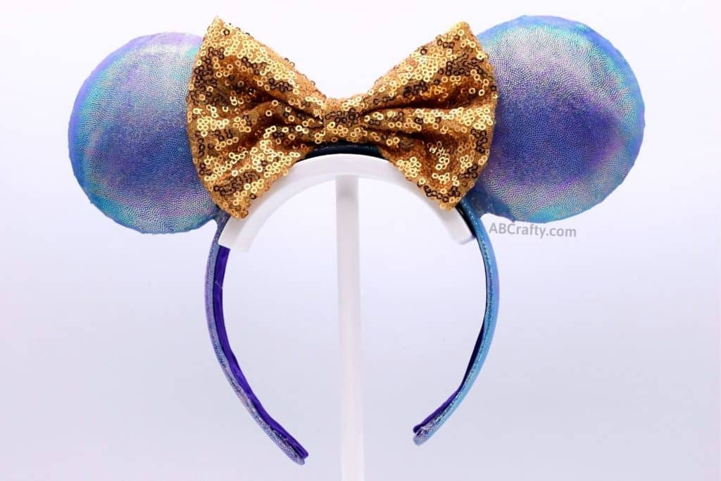 finished disney world 50th anniversary ears that are blue and purple iridescent with a gold sequin bow