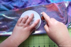 using a rotary cutter to cut around the ab crafty mickey ear template on blue and purple iridescent fabric