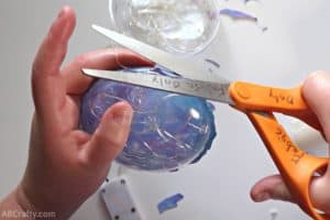 using fabric scissors to cut around blue and purple iridescent fabric glued to a clear plastic ornament