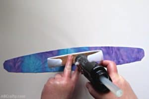 using a glue gun to add glue to the middle of a white headband over iridescent purple and blue fabric