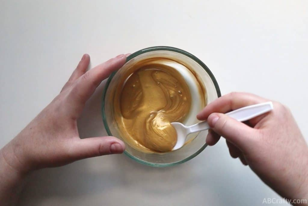 mixing gold liquid in a clear glass bowl with a plastic spoon