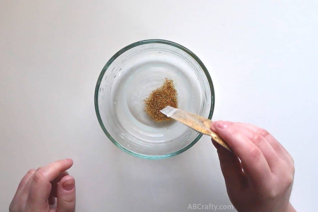 pouring gold glitter into a bowl with clear liquid