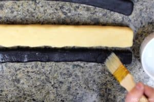 using pastry brush to brush black cookie dough with water