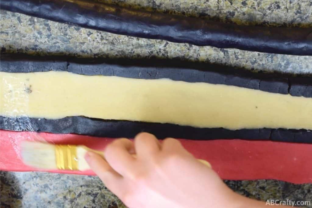 using pastry brush to brush water onto sugar cookie dough