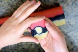 shaping pokemon cookie dough that's in the shape of a pokeball