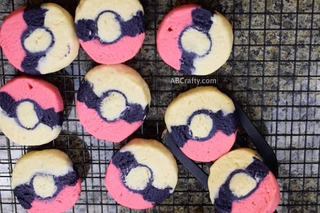 using spatula to put two pokemon cookies onto cooling rack with other pokemon sugar cookies