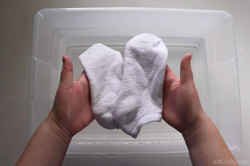 holding two white socks over a plastic bin