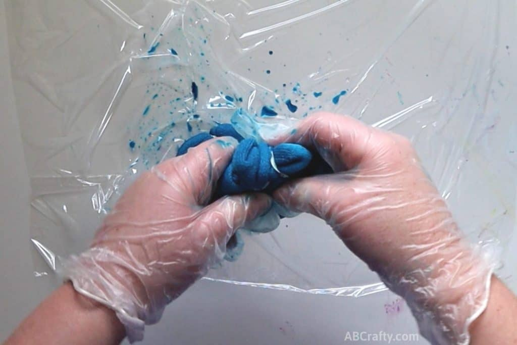 squishing a dyed blue sock while wearing rubber gloves