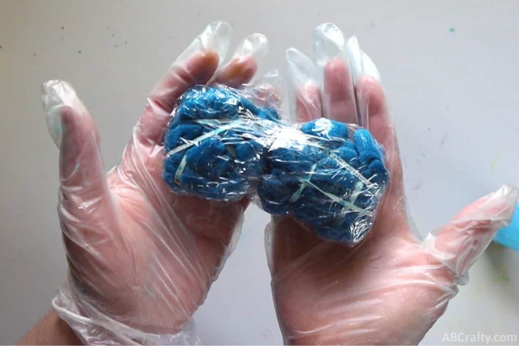 holding blue tie dye socks wrapped in plastic wrap while wearing rubber gloves