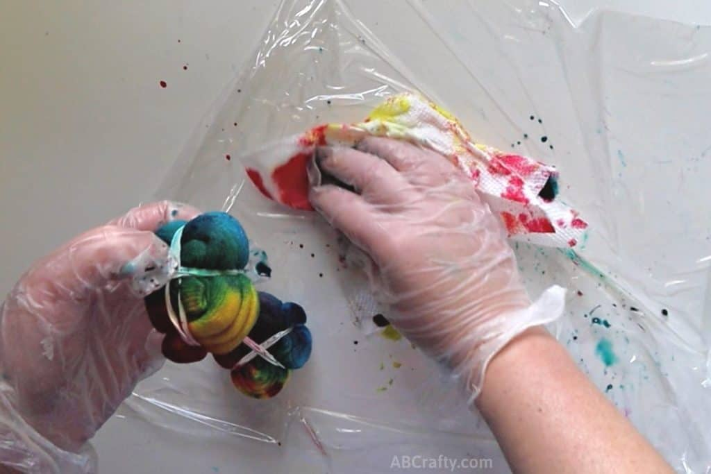using a paper towel to wipe up dye from the plastic wrap while holding rainbow tie dye sock