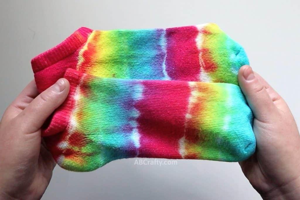 holding two striped rainbow tie dye socks