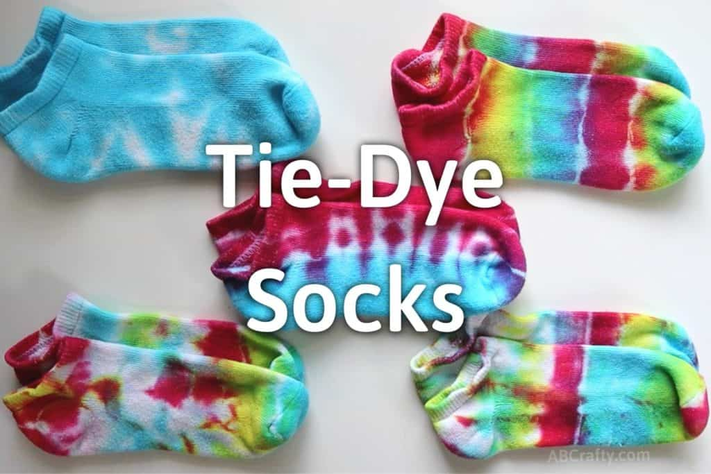 5 piles of tie dyed socks in blue, red and blue, and rainbow with the title of tie dye socks