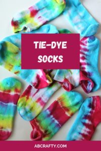 pile of single tie dye socks in different colors with the title tie-dye socks and abcrafty.com