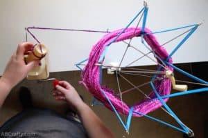 turning the handle of a yarn ball winder to begin winding pink yarn off a yarn swift
