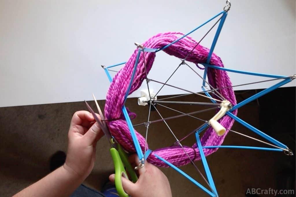 cutting ties off of a hank of yarn that's on a blue plastic yarn swift